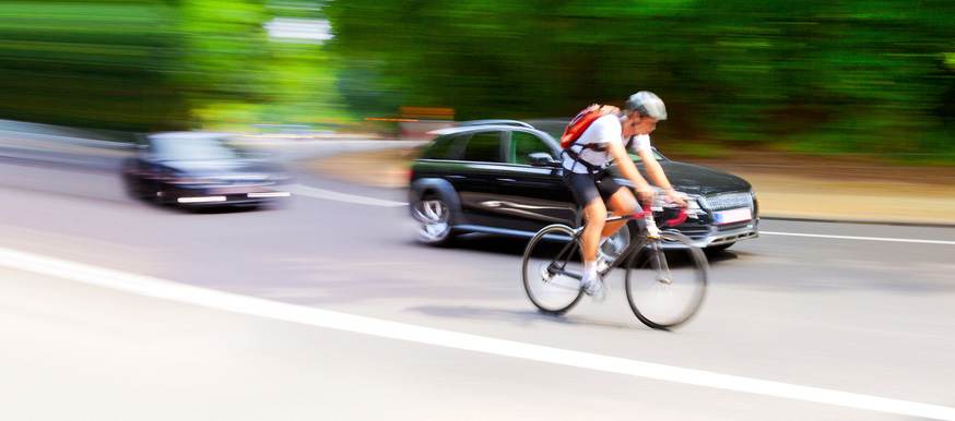 Ciclista en carretera con coches