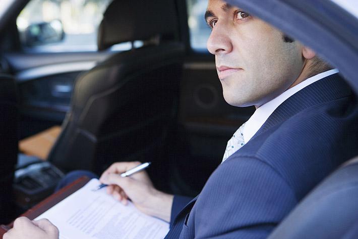 hombre rellenando papeles dentro de un coche